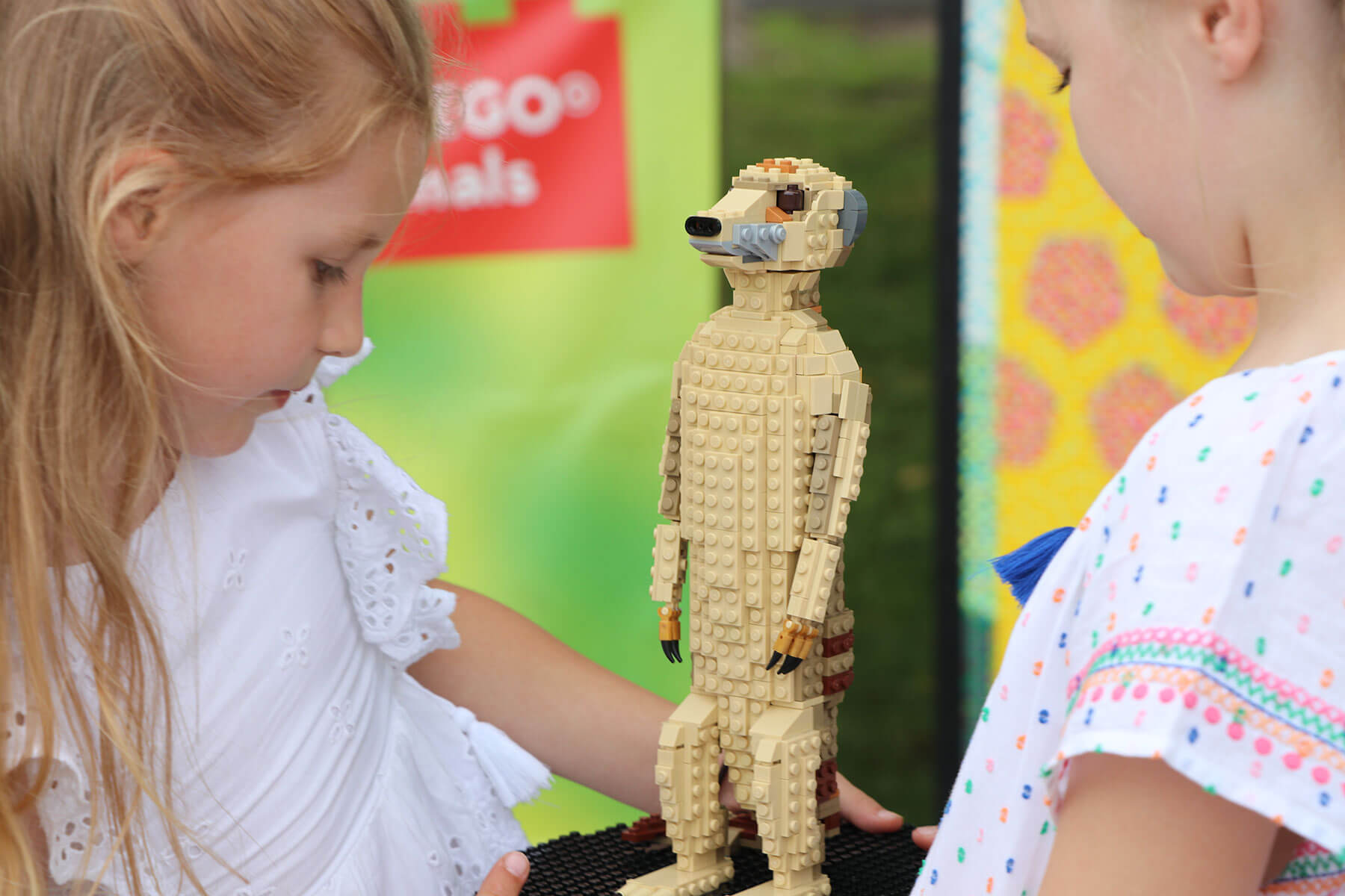 Two children looking at a Meerkat made out of Lego.